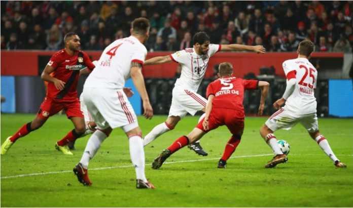 Javi Martinez menghindari dua pemain Bayer Leverkusen untuk memberi Bayern Munchen gol pertama pada laga Liga Jerman di BayArena, Sabtu dinihari