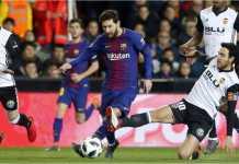 Striker Barcelona Lionel Messi mencoba melepaskan tekanan dari dua pemain Valencia dalam laga leg kedua semi final Copa del Rey, Jumat dinihari.