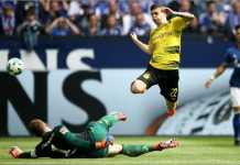 Pemain Dortmund Christian Pulisic melompat untuk menghindari terjangan kiper Schalke Ralf Faehrmann pada laga bigmatch Liga Jerman, Minggu malam WIB.