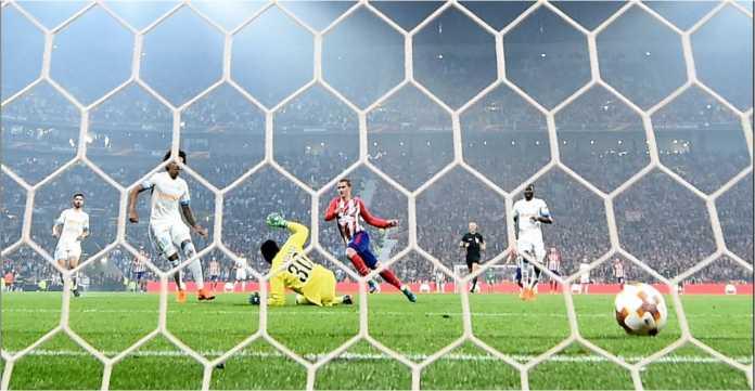Striker Atletico Madrid Antoine Griezmann mengecoh penjaga gawang Marseille untuk melesakkan gol pada laga final Liga Europa, Kamis dinihari.