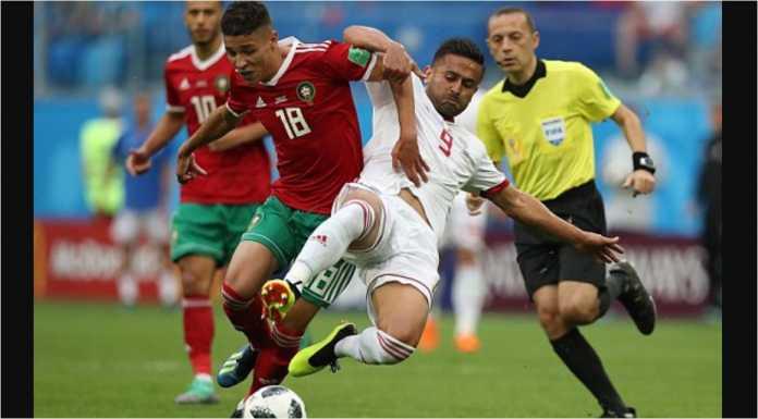 Amine Harit dari Morocco ditekel oleh Omid Ebrahimi (Iran) dengan wasit Cuneyt Cakir asal Turki menyaksikan dari arah belakang.