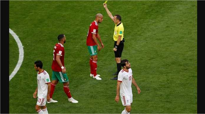 Karim El Ahmadi dari Maroko menerima kartu kuning dari wasit Cuneyt Cakir (Turki) pada babak pertama laga Maroko vs Iran, Jumat malam.