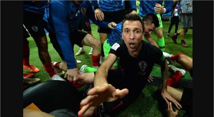 Mario Mandzukic minta maaf pada fotografer AFP yang menangkap momen ini, setelah perayaan gol kedua Kroasia atas Inggris menyebabkan sejumlah pemain menindihnya di pinggir lapangan.