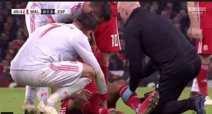Berita Bola - Ethan Ampadu saat cedera di laga Timnas Wales kontra Spanyol, dan tampak dikelilingi dua seniornya di Chelsea; Alvaro Morata dan Cesar Azpilicueta.